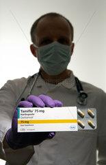 Berlin  Deutschland  ein Arzt mit Mundschutz haelt eine Packung des Medikaments Tamiflu