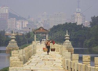 China  Fujian province  Quanzhou area Woman carrying balance pole on Aning bridge