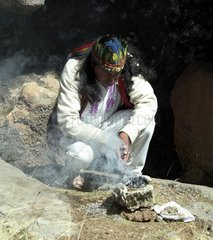 Peru  Cuzco  Sacsayhuaman Inca ruin  priest celebrating a shamanism during the mass in a cave