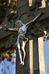 altes steinernes Wegkreuz mit verwittetem gekreuzigtem Jesus Christus