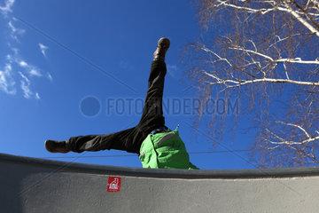 Berlin  Deutschland  Kind schlaegt ein Rad auf einer Mauer