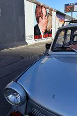 Berlin  Deutschland  der BRUDERKUSS an der East Side Gallery  im Vordergrund ein Trabi