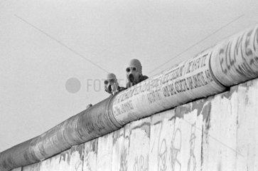 DDR-Grenzsoldaten mit Gasmasken auf der Mauer