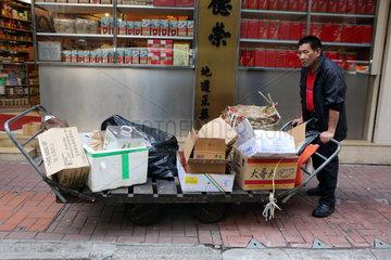 Hong Kong  China  Mann sammelt Kartons auf einer Strasse ein
