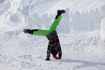 Obertraun  Oesterreich  Junge schlaegt im Schnee ein Rad
