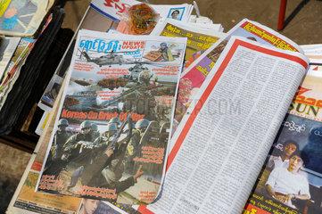 Yangon  Myanmar  Strassenhaendler verkauft Zeitungen
