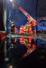Berlin  Deutschland  Einsatzfahrzeug der Feuerwehr spiegelt sich in einer Pfuetze