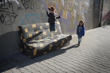 Berlin  Deutschland  Kinder huepfen auf einer alten Couch