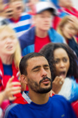 Sports enthusiasts looking upset during sports match