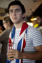 British football fan watching match in bar with flag draped around neck