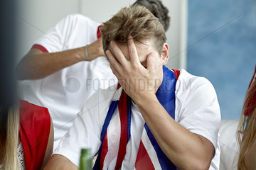 British football fan covering face with hand while watching match