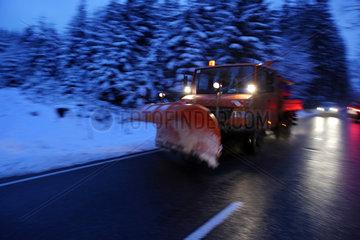 Schleiz  Deutschland  Schneeraeumfahrzeug bei Daemmerung auf einer Landstrasse
