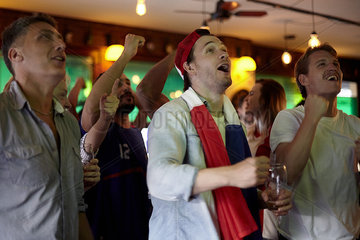 French football fans watching match in bar