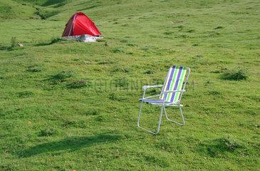 Morzine  Frankreich  Campingstuhl und Zelt stehen auf einer gruenen Wiese