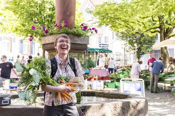 Frau mit frischem Gemuese auf dem Wochenmarkt