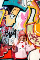 Berlin  Deutschland  ein junges Maedchen vor einer mit Graffiti bemalten Wand