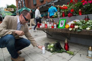 Posen  Polen  ein Mann zuendet eine Trauerkerze am Tatort eines Mordes in der Fussgaengerzone an