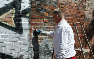 Berlin  Deutschland  Entfernung von Graffiti an einer Backsteinmauer