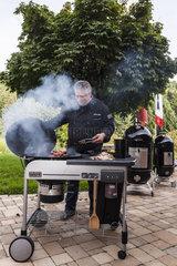 Mann grillt mit Smoker-Grill