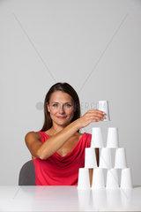 Freiburg  Deutschland  eine junge Frau baut eine Pyramide aus Pappbechern