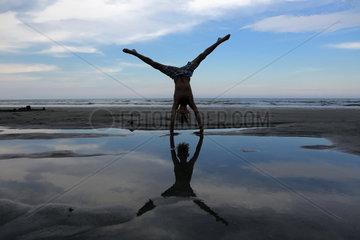 Cocoa Beach  USA  Junge macht am Strand einen Handstand