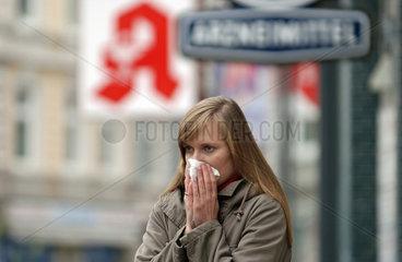 Frau mit Schnupfen vor Apotheke