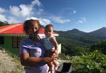 Laudat  Dominica  eine Grossmutter mit ihrem Enkelkind am Strassenrand