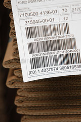 Berlin  Deutschland  Komissionszettel an einem Stapel Faltkartons mit Barcodes