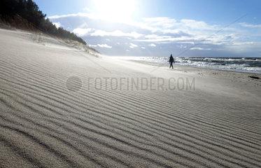 Kolberg  Polen  Frau laeuft bei Sonnenschein allein am Strand entlang