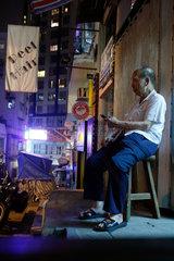 Hongkong  China  ein alter Mann sitzt in den Strassen von Hong Kong und hoert Musik