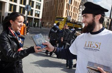 Berlin  Deutschland  Mann ueberreicht einer Passantin den Koran