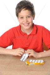 Kind packt Tabletten aus