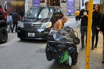 Hong Kong  China  Mann sammelt Muell auf einer Strasse ein