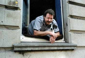 Mann mit Hund liegt im Fenster