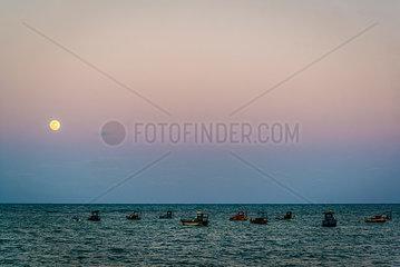 Boote bei Vollmond auf dem Meer