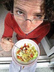 Junge Frau isst Salat