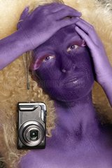 A woman is bodypainted and is holding a camera in her hand.