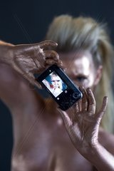 A woman is bodypainted and takes a photo of herself.