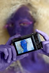 A woman is bodypainted and is holding a camera in her hands.