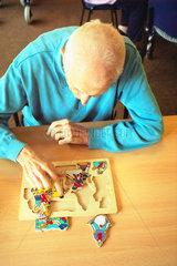 Demenzkranker Mann puzzelt