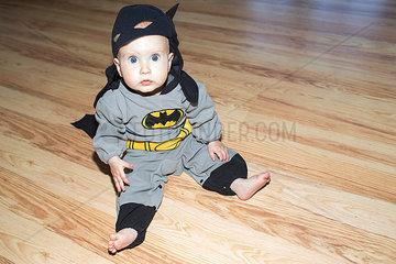 Kleinkind mit Batmankostuem sitzt auf Boden