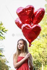 Weiblicher Teenager mit Luftballons in Herzform