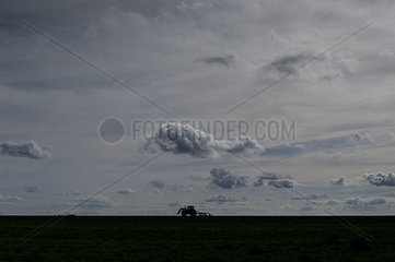 Silhouette eines Traktors und Wolkengebilde in der Abenddaemmerung