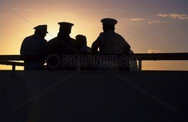 Sailors on cruise ship at sunset