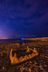Sandburg am Strand bei Nacht