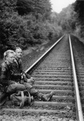 Zwei Punks sitzen im Abendlicht auf Bahngleisen