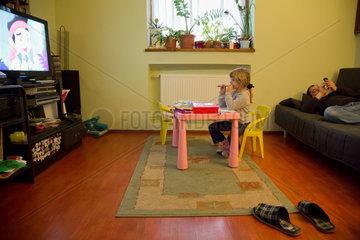Breslau  Polen  ein Maedchen schaut eine Zeichentrickserie im Fernsehen  ihr Vater liegt auf dem Sofa