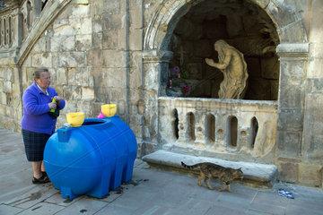 Lemberg  Ukraine  eine Frau trinkt geweihtes Wasser vor der St.-Georgs-Kathedrale