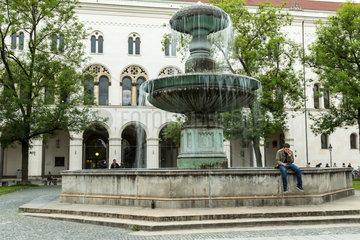 Muenchen  Deutschland  Student sitzt am Brunnen am Geschwister-Scholl-Platz