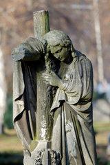 Berlin  Deutschland  trauernde Figur am Kreuz auf dem Friedhof am Suedstern